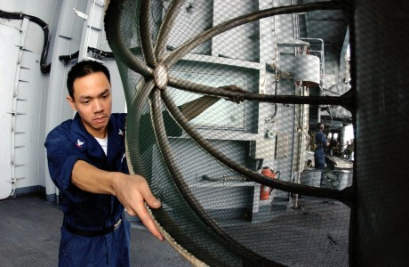 US Navy 050728-N-0413R-077 Aviation Machinist's Mate 3rd Class Jalvin Yuchongtian, inspects the cover for an J-52 engine