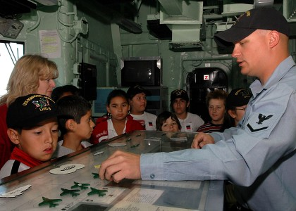 US Navy 070330-N-5567K-084 An aviation boatswain^rsquo,s mate describes take off and landing planning and tracking procedures to a group of 5th grade students from Gerald R. Ford Elementary
