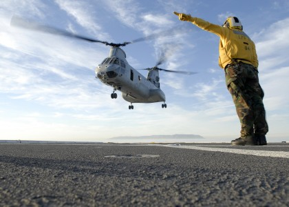 US Navy 101105-N-2515C-126 Aviation Boatswain Mate (Handling) 3rd Class Troy Palomino signals a CH-46E Sea Knight helicopter to take off