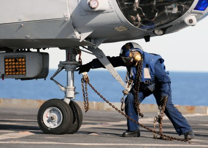 US Navy 110225-N-RC734-165 Boatswain's Mate 3rd Class Lakeiha Henderson, from New York, removes a tie-down chain from the nose wheel of a CH-46E Se