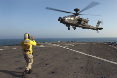 US Navy 120128-N-KS651-305 A Sailor signals a helicopter to land on the flight deck of USS Pearl Harbor
