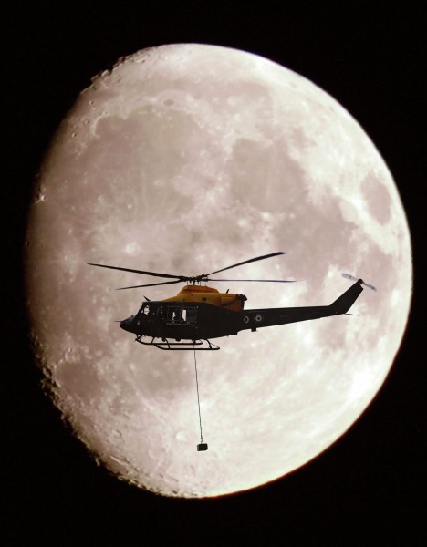 A Griffin Helicopter, with an underslung load, shown in silhouette against a full moon