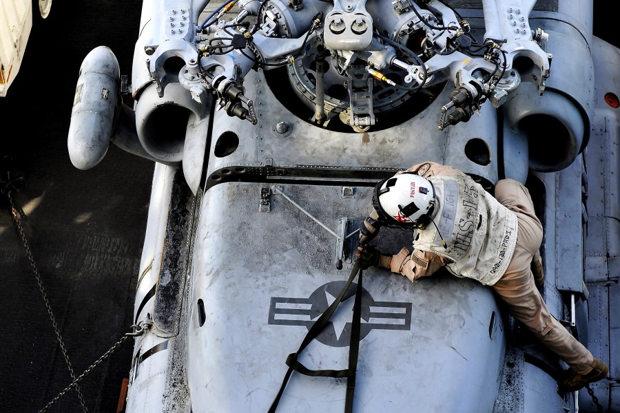 Defense.gov News Photo 120208-N-UT411-686 - U.S. Navy Lt. j.g. Julian Pascuzzi inspects an HH-60H Sea Hawk helicopter before flight operations aboard the aircraft carrier USS Carl Vinson CVN