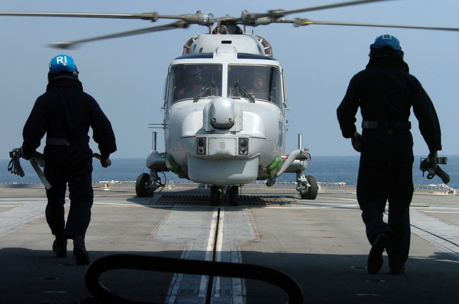 US Navy 050220-N-1444C-038 Two Royal Navy Sailors prepare to chain-down a Royal Navy Lynx Mk8 helicopter, assigned to 815 Squadron aboard the Royal Navy Type 23 frigate HMS Grafton (F80)