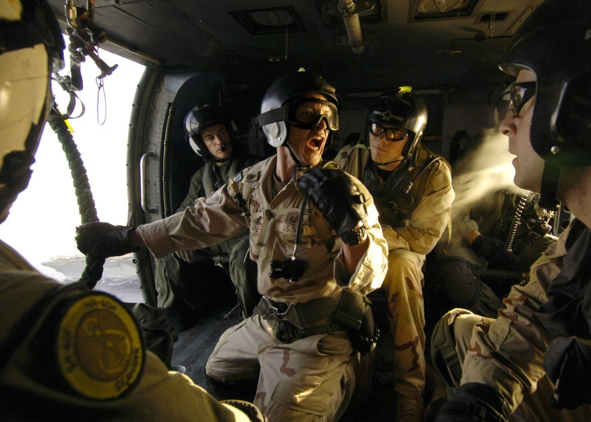 US Navy 060530-N-9742R-215 Senior Chief Electronics Technician Rick Straney, center, assigned to Explosive Ordnance Disposal Mobile Unit Six (EODMU-6) Detachment 14, shouts orders to members
