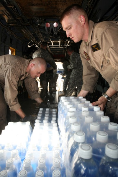 US Navy 071126-M-7696M-108 Cpl. Eric M. Dorfman, right, and Cpl. Nicholas M. Moneymaker load cases of bottled water onto a CH-53E Sea Stallion transport helicopter