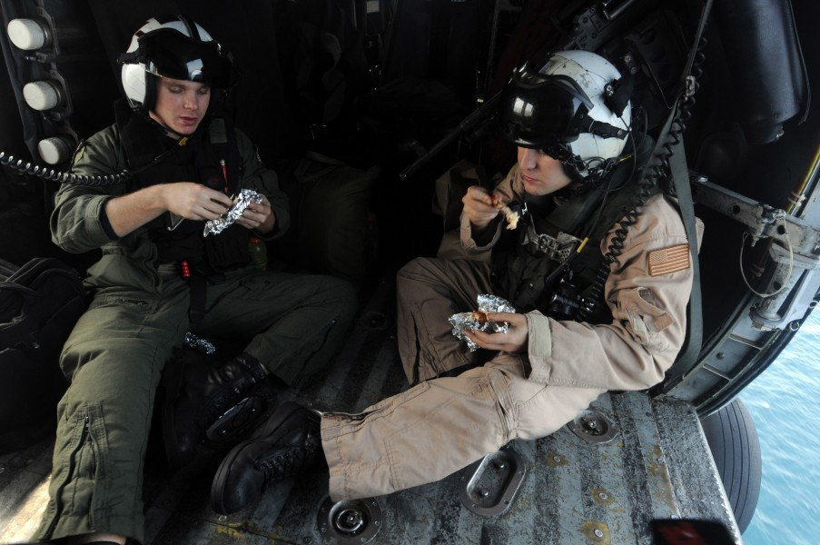 US Navy 081013-N-3659B-018 Aviation Warfare Systems Operator 3rd Class Matthew Anderson, left, and Aviation Warfare Systems Operator 2nd Class Adam Walker take a moment to eat their lunches in an HH-60H Sea Hawk