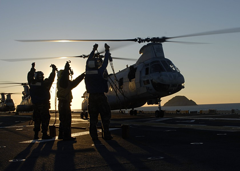 US Navy 090715-N-5215E-124 Aviation Boatswain's Mates (Handling) show their chocks and chains to the pilot of a CH-46E Sea Knight helicopter