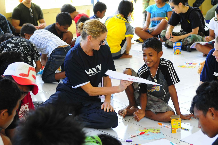 US Navy 100714-N-6410J-196 New Zealand Defense Force Lt. Cmdr. Kerry Climo gives a boy a paper airplane she made while spending time with children at the Rumah Sejahtera Bagi Anak Orphanage