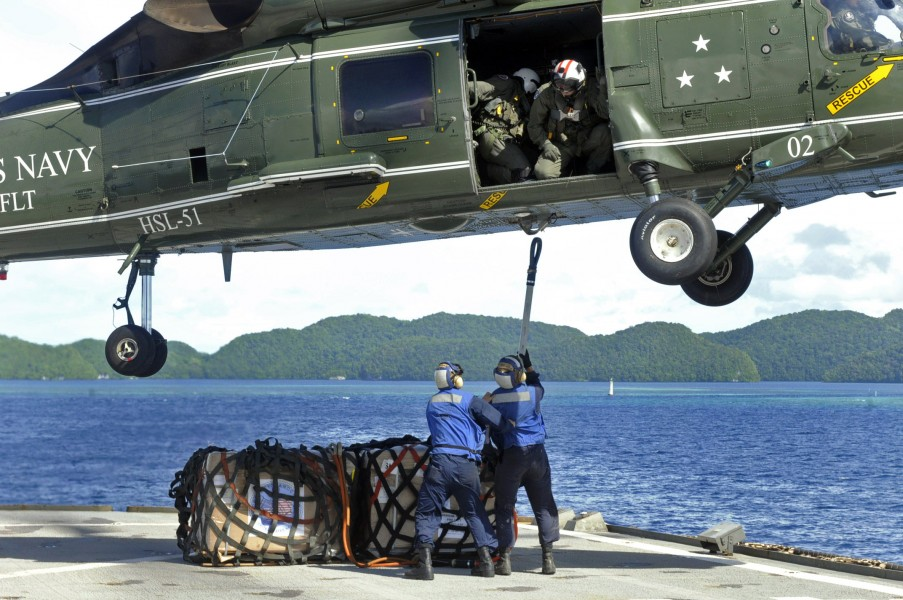 US Navy 100726-N-7478G-212 Sailors attach Project Handclasp materials to an SH-60F Sea Hawk helicopter aboard the U.S. 7th Fleet command ship USS Blue Ridge (LCC 19)