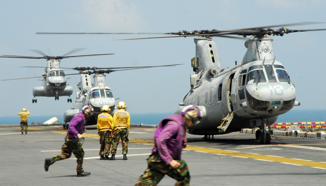 US Navy 110213-N-8607R-393 Aviation fuel crew members run to fuel a CH-46E Sea Knight helicopter aboard the forward-deployed amphibious assault shi