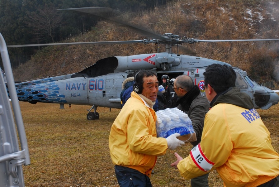 US Navy 110316-N-SB672-114 Japanese citizens unload food and water from an HH-60H Sea Hawk helicopter assigned to the Black Knights of Helicopter A