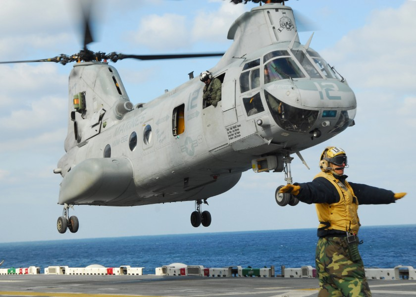 US Navy 110318-N-8607R-183 Aviation Boatswain's Mate Airman Daniel Moreno directs a CH-46E Sea Knight helicopter to take off from the flight deck o