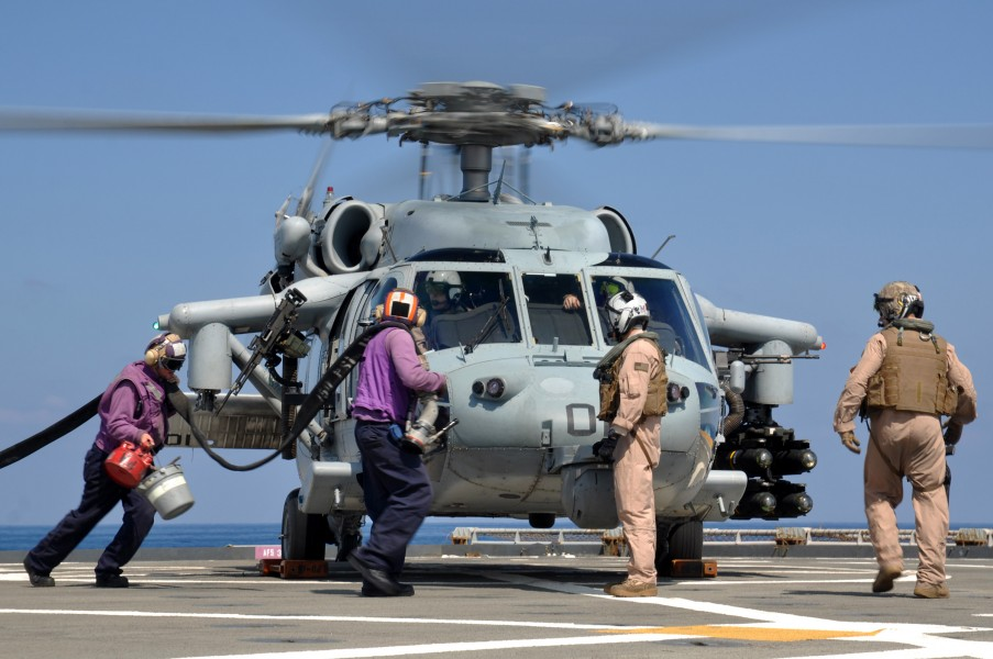 US Navy 110325-N-7293M-126 Sailors run to refuel an MH-60S Sea Hawk helicopter