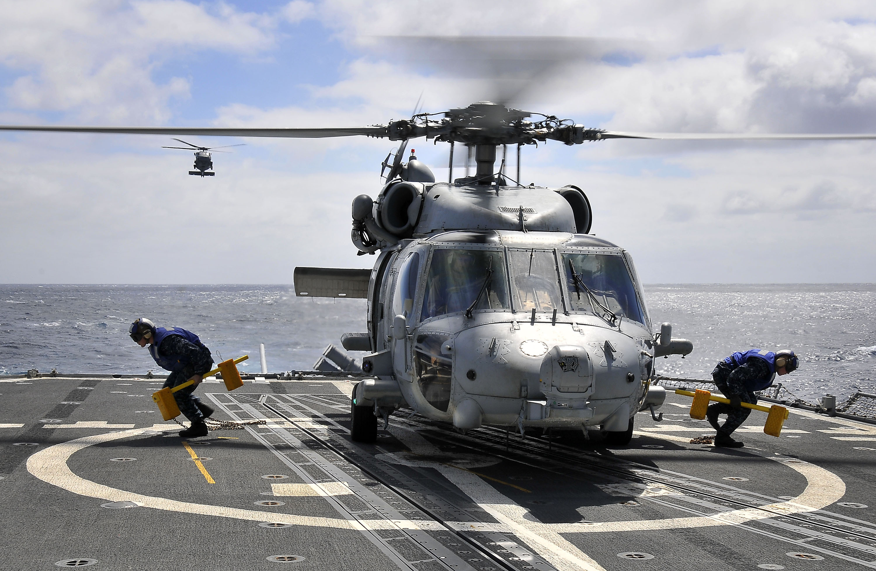 US Navy 100321-N-4774B-132 Sailors remove the chock and chains securing an SH-60F Sea Hawk helicopter assigned to the Red Lions of Helicopter Anti-submarine Squadron (HS) 15