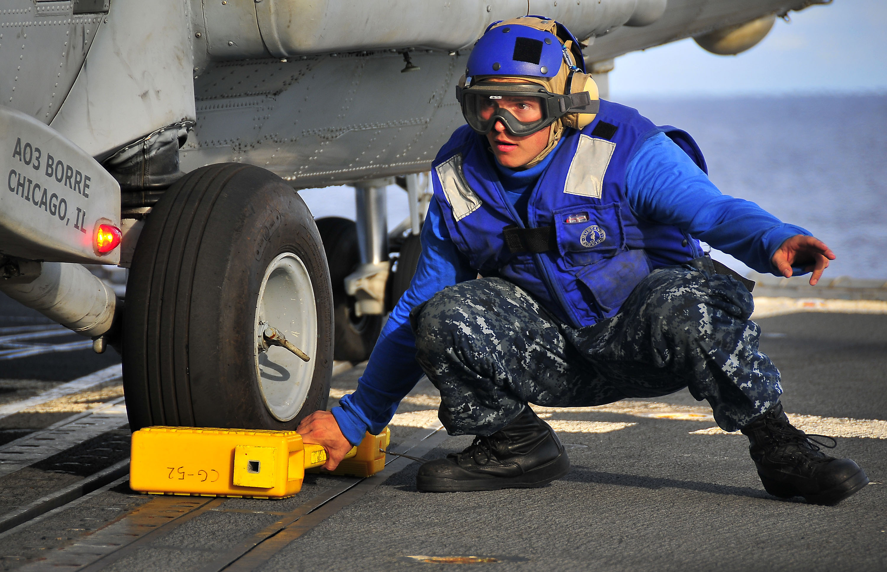 US Navy 100406-N-4774B-604 Boatswain's Mate Seaman Apprentice Anthony Orduna prepares to remove a chock from the landing gear of an SH-60F Sea Hawk helicopter