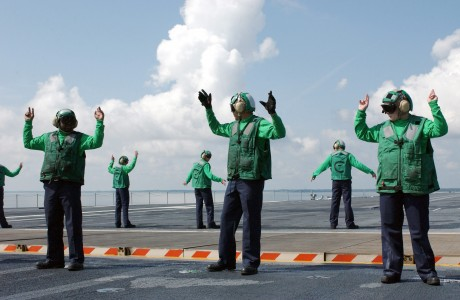 US Navy 040427-N-8148A-039 Crew members assigned to V-2 division aboard USS Ronald Reagan (CVN 76) signal to raise and lower Jet Blast Deflectors