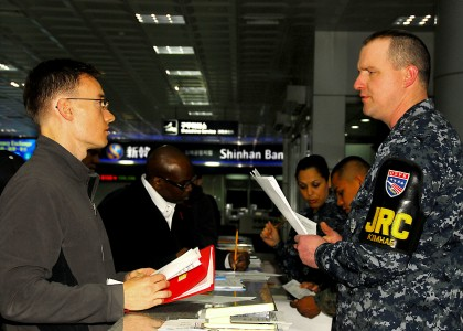 US Navy 100306-N-9573A-018 Equipment Operator 2nd Class Daniel O'Bryant helps a Sailor at Gimhae International Airport during Key Resolve-Foal Eagle 2010