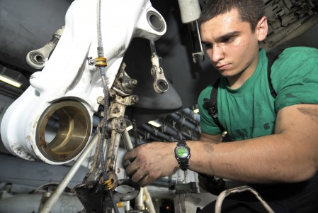 US Navy 100624-N-6003P-092 Aviation Structural Mechanic 3rd Class Donald Elder replaces an axle lever on the landing gear of an F-A-18C Hornet aboard the aircraft carrier USS Harry S. Truman (CVN 75)