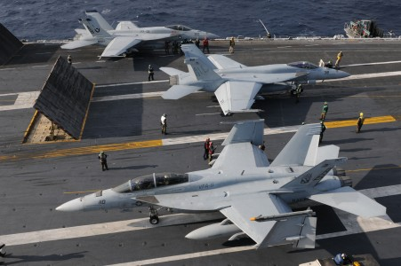 US Navy 101209-N-9693M-009 Two F-A-18E Super Hornets prepare for a catapult assisted launch as an F-A-18E Super Hornet taxis toward the aft of USS