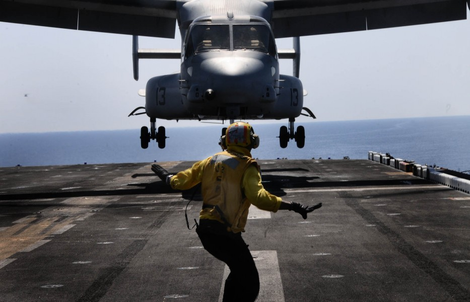 Defense.gov News Photo 110511-N-7508R-002 - A landing signal enlisted assigned to the multipurpose amphibious assault ship USS Bataan LHD 5 guides an MV-22B Osprey assigned to Marine Medium