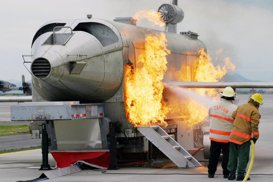 US Navy 040303-N-5821W-001 Personnel at NAS Sigonella's Fire Department battle a fire while training with the a Mobile Aircraft Fire Trainer (MAFT)