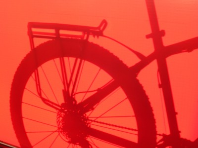 Silhouette of a bike leaning against a red canvas.