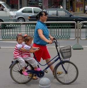 Woman pushing a bike with two kids