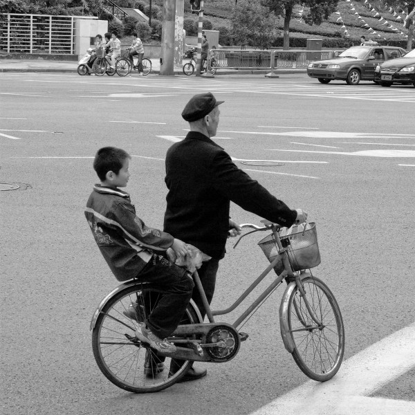 A man is holding cycle with kid