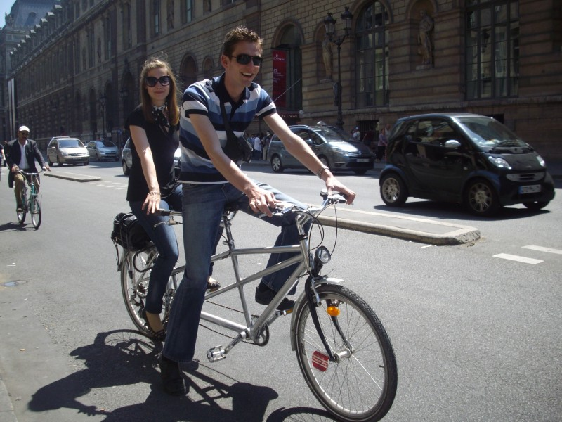 A couple bicycling on the streets of Paris near the Louvre Museum