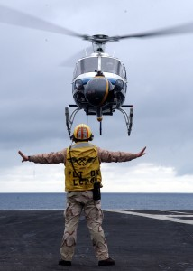 US Navy 040128-N-3241H-018 Chief Aviation Boatswain's Mate Glenn Harrison guides a commercial aerial filming helicopter safely to the flight deck aboard USS Carl Vinson (CVN 70)