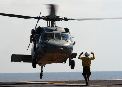 US Navy 040423-N-9742R-004 Aviation Boatswain's Mate 3rd Class Ifoma Givens, of Philadelphia, Pa., directs an MH-60S Knighthawk