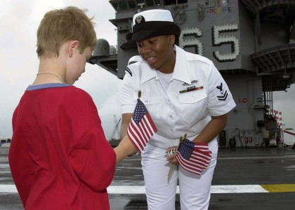 US Navy 040429-N-6268K-012 Intelligence Specialist 2nd Class Tashawbaba McHerrin hands an American flag to a child on the ship's flight deck