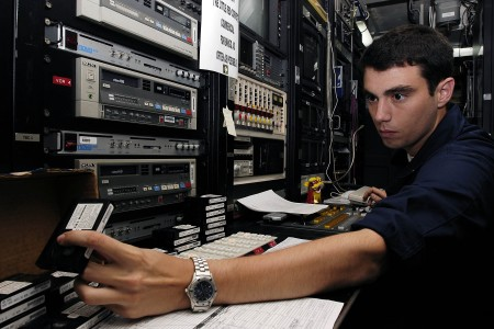 US Navy 050211-N-4166B-028 Journalist 3rd Class Michael Hart of Kingston, Tenn., grabs a video tape which will be played on the closed circuit television system ran by the Journalists twenty-four hours a day