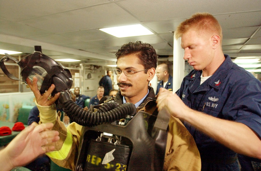 US Navy 020924-N-4309A-030 Damage Controlman assists with the firefighting gear of Pakistani Lieutenant from the Pakistani ship Tippu Sultan (DDG 185)