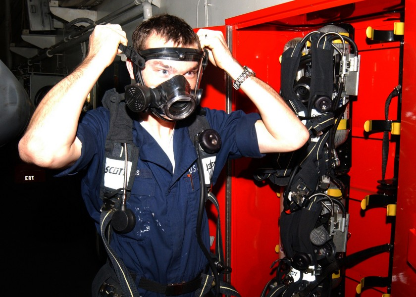 US Navy 021102-N-6817C-005 Damage Controlman Fireman Aaron Williams, of Amarillo, Texas, checks for the proper fit on a face mask on a Self Contained Breathing Apparatus (SCBA)