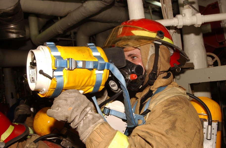 US Navy 021104-N-0685W-002 Damage Controlman during a General Quarters (GQ) drill, checks a space for fire using a hand held thermal Imager