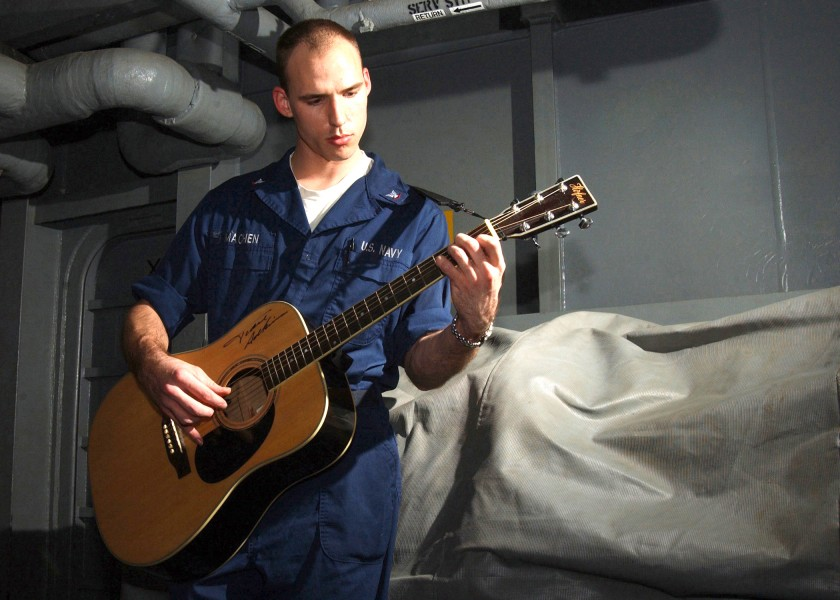US Navy 021201-N-6817C-001 Sailor enjoys playing his guitar during some leisure time aboard the aircraft carrier USS Abraham Lincoln (CVN 72)