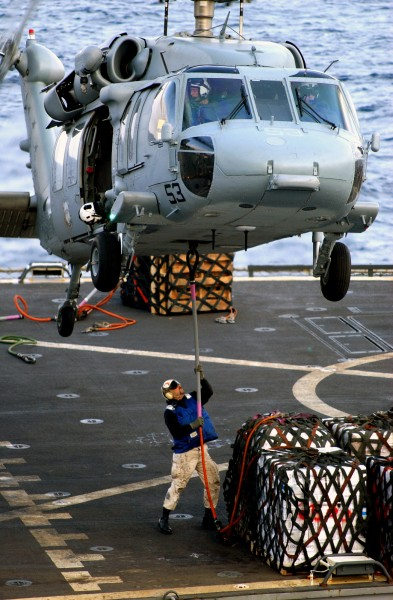 US Navy 030206-N-5821P-009 A Sailor assigned to the combat stores ship USNS San Jose (T-AFS 7) attaches a hoist line to the bottom of an SH-60 ^ldquo,Seahawk^rdquo,