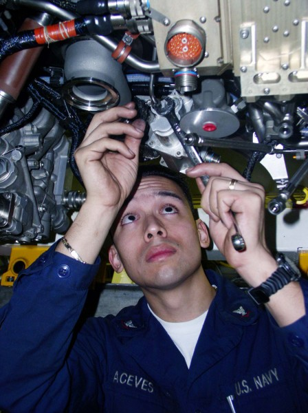 US Navy 030210-N-9228K-015 Aviation Machinist's Mate 3rd Class Anthony Aceves torques a nut on the engine of an F-A-18E Super Hornet