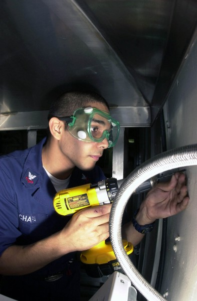 US Navy 030401-N-1577S-002 Hull Technician 2nd Class David Chapa from Pleasanton, Texas, lines up his drill to begin installation of an electrical outlet aboard USS Nimitz (CVN 68)