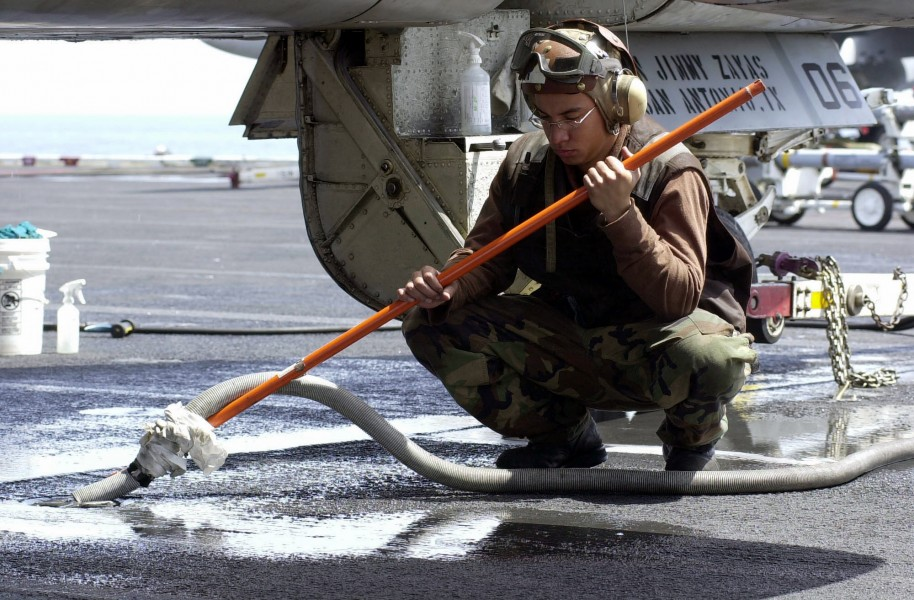 US Navy 030414-N-9319H-005 Airman Apprentice Jimmy Zayas from San Antonio, Texas, vacuums out water from a pad eye
