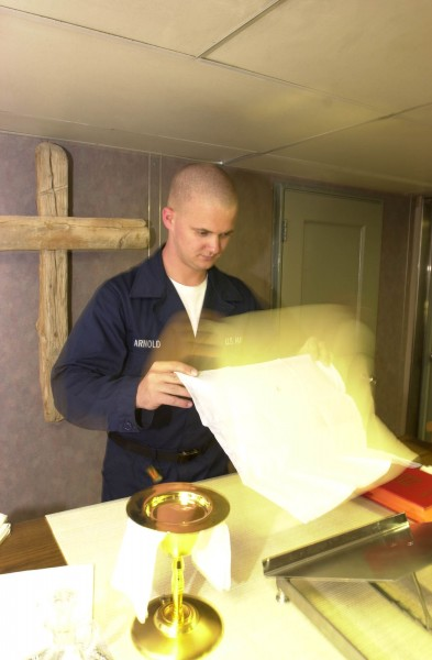 US Navy 030514-N-0413R-006 Religious Program Specialist Seaman Derek Arnold of Ripon, Wis., prepares for a Catholic mass in the Chapel aboard USS Nimitz (CVN 68)