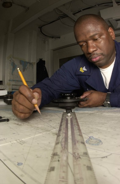 US Navy 030519-N-1577S-001 Quartermaster 1st Class Anthony Glover of Chicago Ill., checks the accuracy of a nautical map that is used to navigate USS Nimitz (CVN 68)