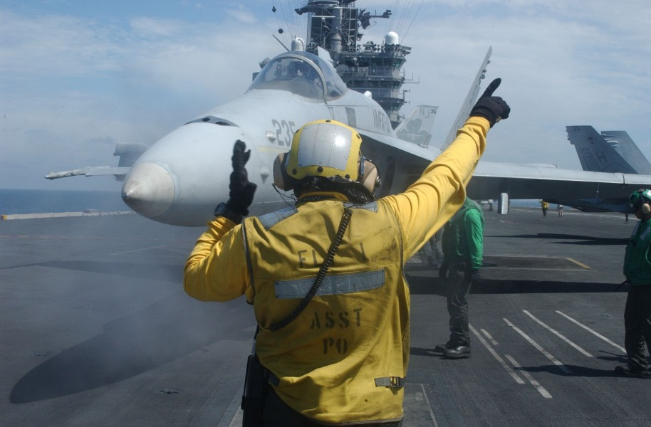 US Navy 030729-N-7732W-262 An Aviation Boatswain's Mate directs an F-A-18 Hornet onto a steam catapult during flight operations aboard USS John C. Stennis (CVN 74)