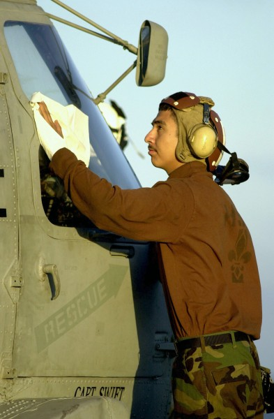 US Navy 030802-N-6213R-460 Aviation Machinist's Mate Airman Jose Padilla cleans the windshield of an SH-60F Seahawk