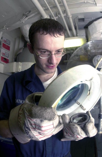 US Navy 030903-N-2143T-001 Aviation Structural Mechanic Airman John Watkins uses a magnifying glass to check for defects