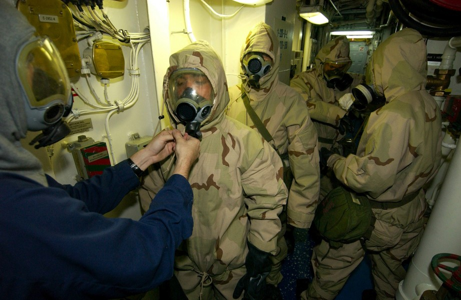 US Navy 030920-N-5471P-004 Damage Controlman 3rd Class Michael Muskett helps Ship's Serviceman 3rd Class Daniel Olaya don chemical protective gear