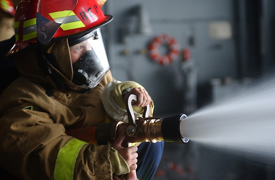 US Navy 031018-N-8295E-319 Rachel Vata, from Superior, Colo., mans a fire hose during a damage control demonstration held in the USS Ronald Reagan (CVN 76) hangar bay