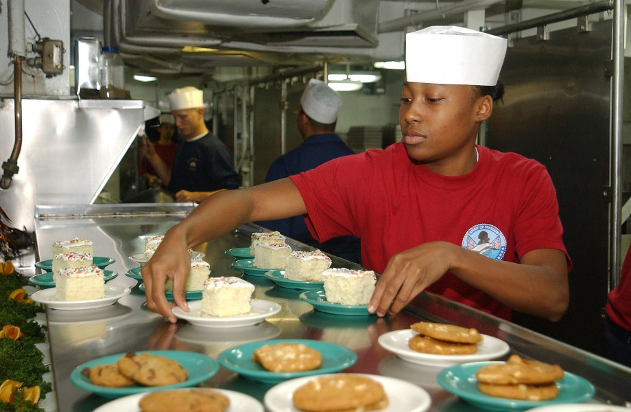 US Navy 031020-N-1127G-001 Seaman Elivian Clark, from Atlanta, places desserts out on the chow line aboard USS George Washington (CVN 73)